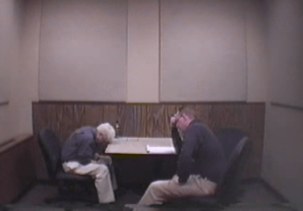 Dr. Bill Hunter rests head on table during a police interview.