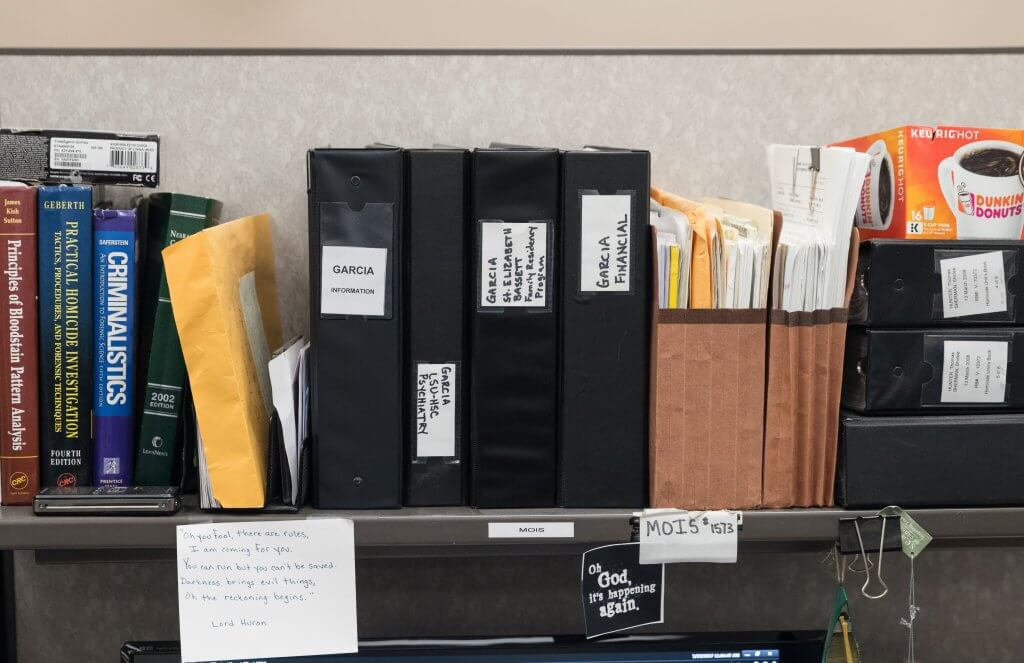 Detective Derek Mois and the binders of information about Anthony Garcia at his desk. Omaha Police Department detectives spent years working on murder cases which resulted in the apprehension and conviction of Anthony Garcia.  Matt Miller/The World-Herald