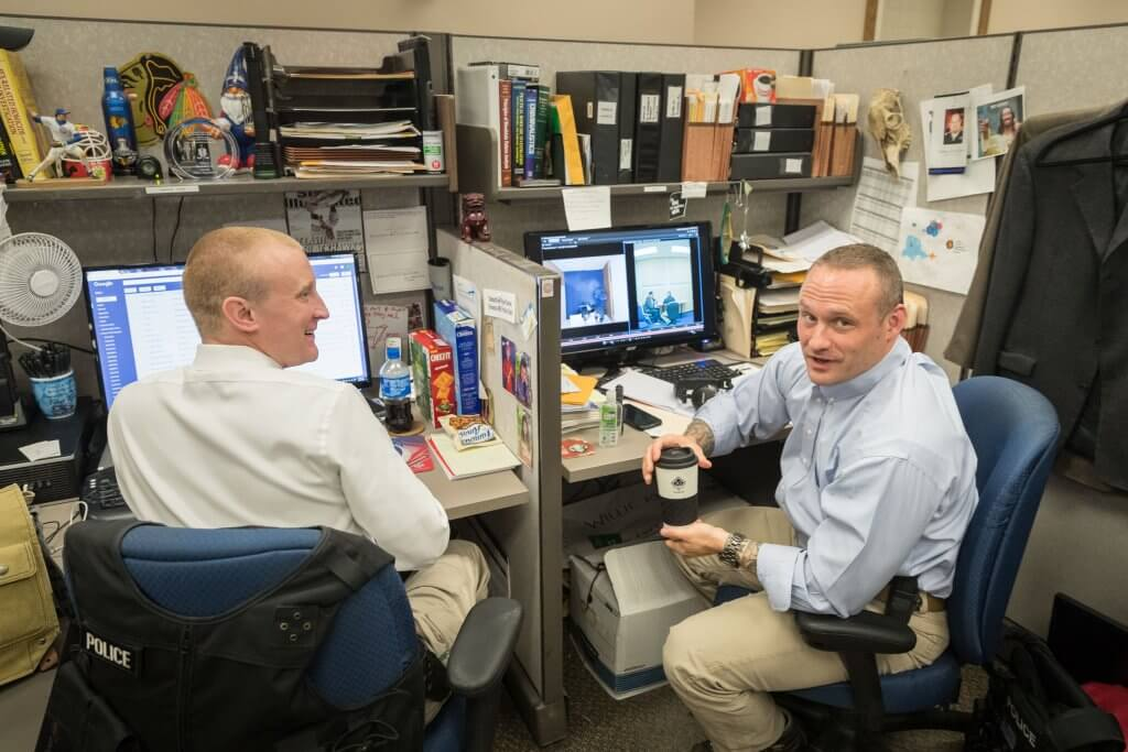 Detectives Ryan Davis, left, and Derek Mois worked in close quarters to solve the murder cases.  Matt Miller/The World-Herald
