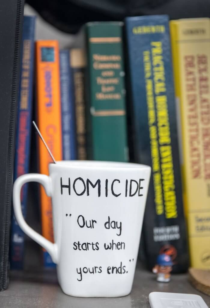 21.	Detective Ryan Davis's coffee mug is set on his bookshelf. Matt Miller/The World-Herald